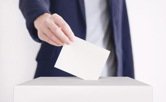 man placing voting card in box