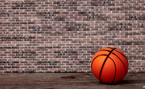 basketball on floor in front of brick wall