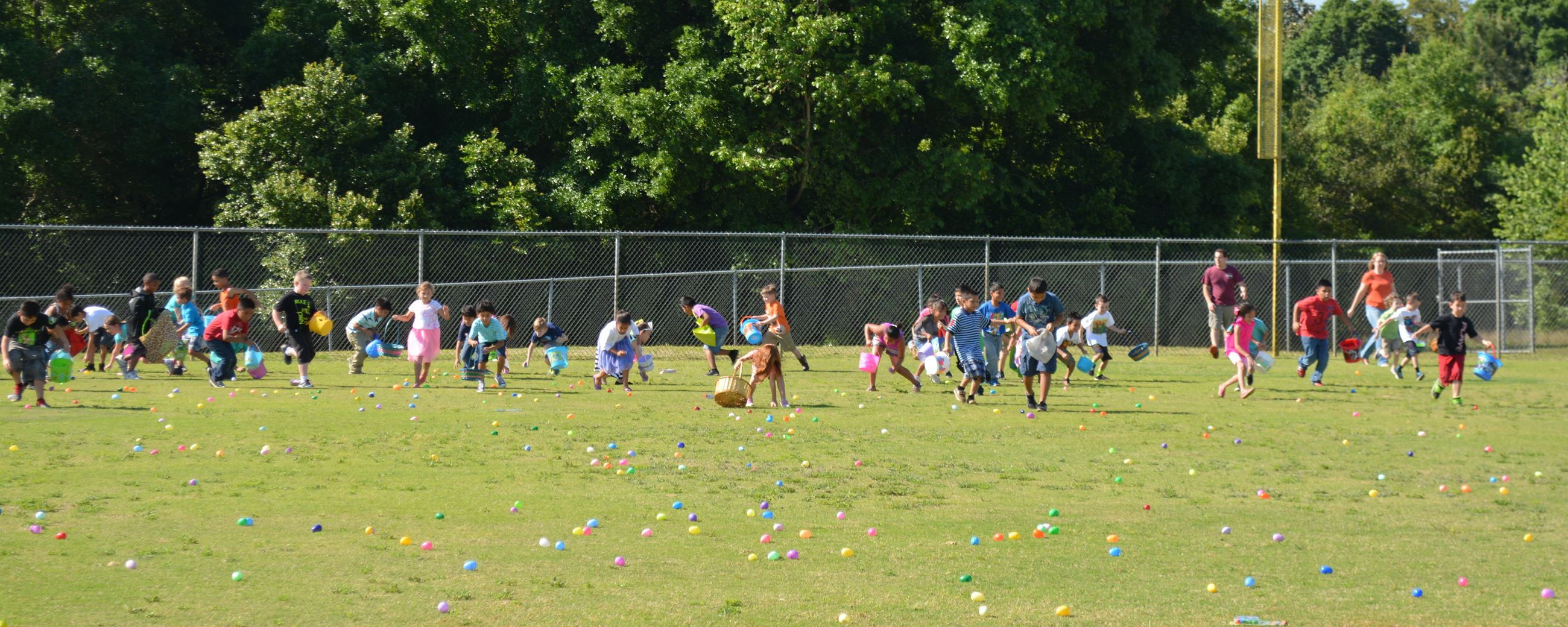 Kids gathering Easter eggs out on the field. (image)